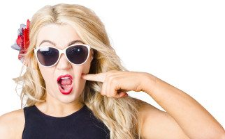Crazy isolated portrait of a shocked blonde woman wearing sunglasses with pin-up makeup pressing cheek in a depiction of cosmetic application